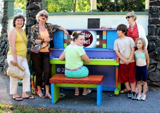 Folks gather to sing around the painted piano